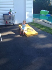 Evelyn sits on a corn hole set -- gosh, she is a cutie!